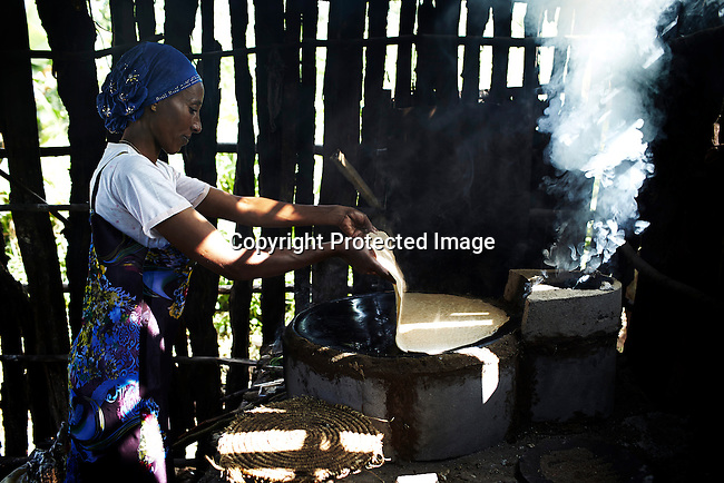 BONGA, ETHIOPIA:  Rukia Mohammed, a mother, makes Injera on a wood burning stove on December 8, 2012 outside Bonga, Ethiopia. This Kaffa region is known for its coffee production, wild coffee grown in high altitudes. This region is the original home of the coffee plant, coffee Arabica which grows in the forest of the highlands. The red berries are the main source of income in the area. Children and cattle also drink coffee. (Photo by: Per-Anders Pettersson)
