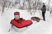 "Sweden, SWE, Kiruna, 2006-Apr-16: Sledging in Lapland: A four years old girl is sitting in a ""Pulka"" while her mother, who pulled the sledge, is standing in the background."