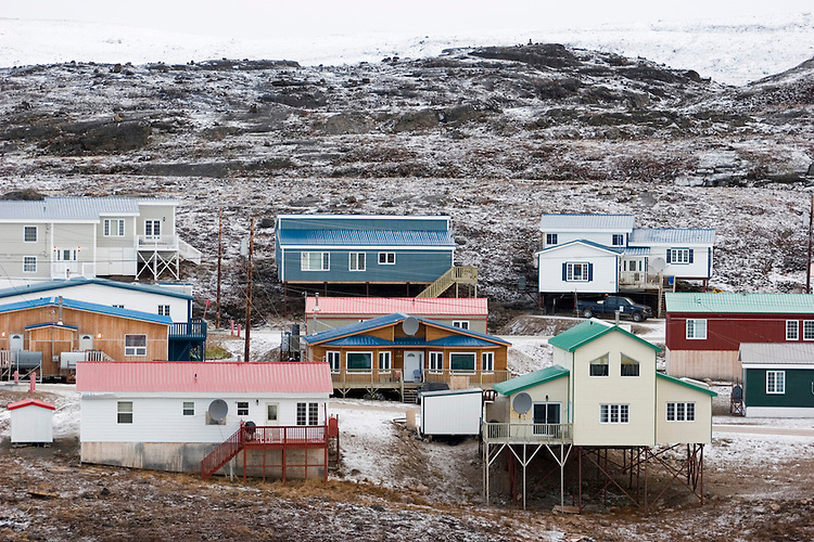 """The Melanson house, center, with white door and TV dish, in Iqaluit, Nunavut, Canada. Iqaluit, with population of 6,000, is the largest community in Nunavut as well as the capital city. It is located in the southeast part of Baffin Island. Formerly known as Frobisher Bay, it is at the mouth of the bay of that name, overlooking Koojesse Inlet. """"Iqaluit"""" means 'place of many fish'. The image is part of a collection of images and documentation for Hungry Planet 2, a continuation of work done after publication of the book project Hungry Planet: What the World Eats, by Peter Menzel & Faith D'Aluisio."""