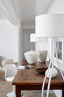 An Eero Saarinen Tulip chair at a wooden table with white floor lamps either side.