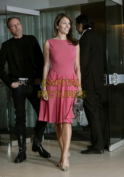 PATRICK COX & ELIZABETH HURLEY.Attend the VIP Ad Campaign Lunch in celebration of designer Patrick Cox's latest ad campaign that Elizabeth Hurley fronts at the Sanderson Hotel, London, UK..February 14th, 2006.Ref: IA.full length pink dress sleeveless silver purse bag.www.capitalpictures.com.sales@capitalpictures.com.©Capital Pictures