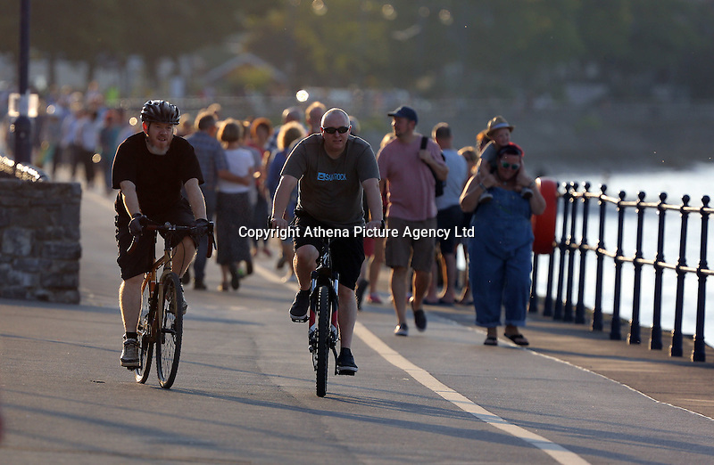 WEATHER PICTURE WALES<br />Pictured: People walk and cycle in the sunshine in Mumbles, south Wales UK. Tuesday 16 August 2016<br />Re: High temperatures and sunshine experienced in most of the UK.