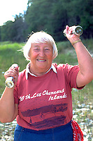 Woman age 70 lifting weights on Lake Huron Les Cheneaux Islands.  Cedarville  Michigan USA