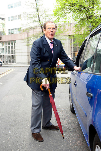 SIR ROGER MOORE .Having a Bond reunion lunch at The Ivy Club this afternoon, London, England..April 26th, 2010.full length blue suit jacket grey gray trousers umbrella car side mouth open.CAP/DYL.©Dylan/Capital Pictures.
