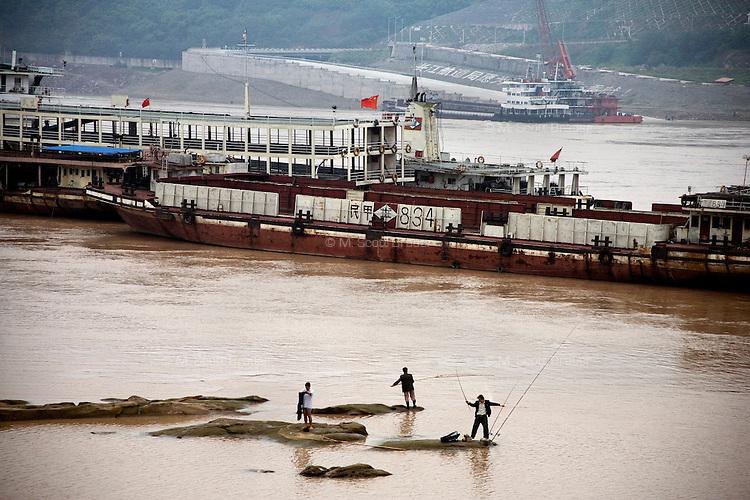 Men fish in the Yangtze River as barges pass by Chongqing, China.