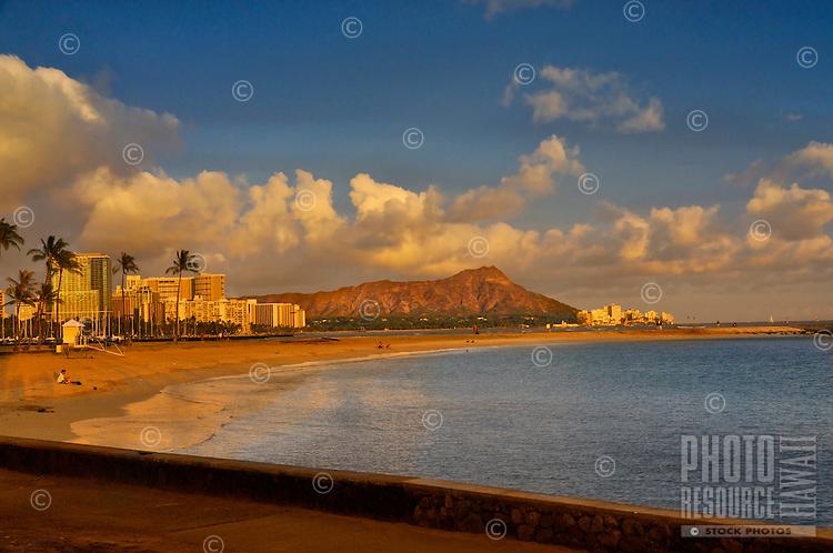 The last rays of the setting sun light up Diamond Head and Waikiki, as seen from Magic Island in Ala Moana Beach Park, O'ahu.