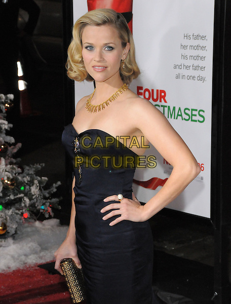 "REESE WITHERSPOON (wearing a Nina Ricci dress).World Premiere of ""Four Christmases"" held at The Kodak Theatre in Hollywood, California, USA..November 20th, 2008                                                                     .4 half length strapless gold necklace hand on hip black navy blue clutch bag .CAP/DVS.©Debbie VanStory/Capital Pictures."