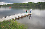 Two boys fishing from a floating dock in Echo Lake in Aroostook State Park, Maine, USA