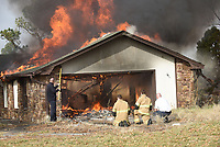 NWA Democrat-Gazette/FLIP PUTTHOFF <br /> TRAINING BURN<br /> Rogers firefighters including Capt. Dennis Thurman (left) stand by a controlled burn Tuesday Feb. 5 2019 of a house on Pleasant Grove Road near Interstate 49. Rogers Fire Department burned two adjacent houses after using them for training purposes. Firefighters from area fire departments and other agencies trained for several days in the two houses before they were ignited, Thurman said.