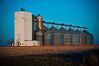 Grain elevator at egg farm bathed in sunset light on a cold winter day with harvested corn field in foreground.