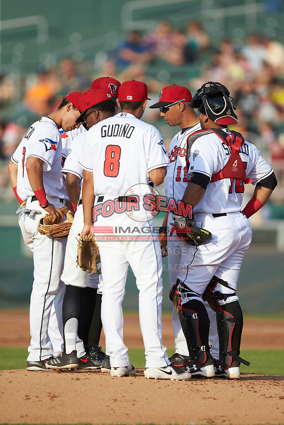 Lansing Lugnuts pitching coach Antonio Caceres (11) has a meeting on the mound during the game against the South Bend Cubs at Cooley Law School Stadium on June 15, 2018 in Lansing, Michigan. The Lugnuts defeated the Cubs 6-4.  (Brian Westerholt/Four Seam Images)
