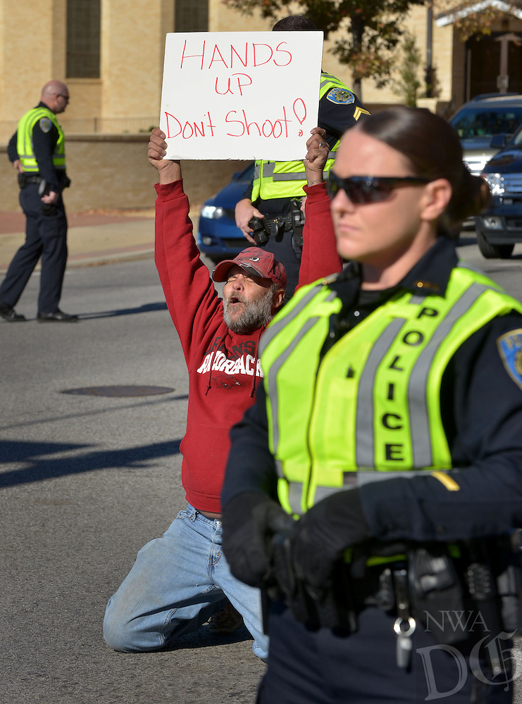 STAFF PHOTO BEN GOFF  @NWABenGoff -- 11/25/14 Austin Ferguson holds a sign reading 'Hands Up, Don't Shoot!' while kneeling in the street during a protest organized by the OMNI Center for Peace, Justice & Ecology in front of the Washington County Courthouse in Fayetteville on Tuesday Nov. 25, 2014. The demonstration was in response to the decision Monday night by the St. Louis County grand jury not to indict police officer Darren Wilson, who fatally shot Michael Brown in Ferguson, Mo.