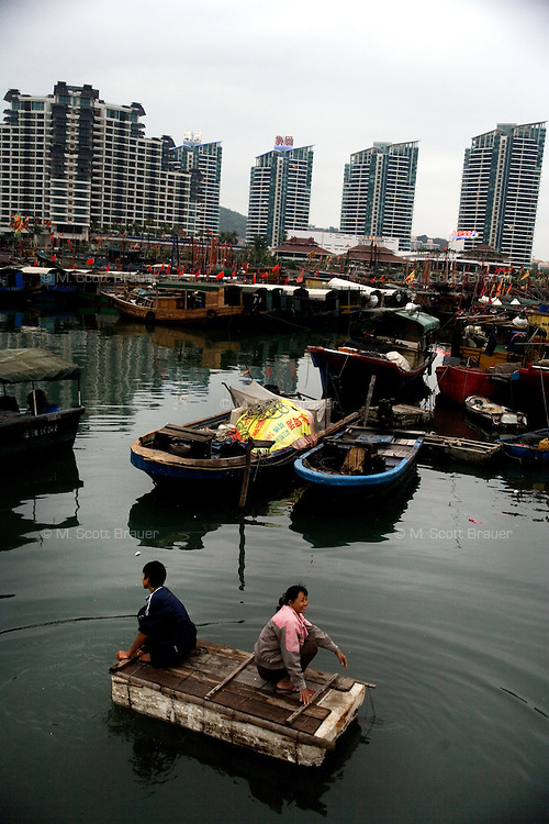 Fishermen ride a homemade styrofoam raft in a marina in Sanya, Hainan, China.