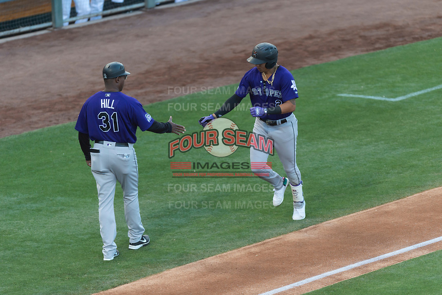 Albuquerque Isotopes center fielder Yonathan Daza (2) is congratulated by manager Glenallen Hill (31) after hitting a home run in the first inning during a Pacific Coast League game against the El Paso Chihuahuas at Southwest University Park on May 10, 2019 in El Paso, Texas. Albuquerque defeated El Paso 2-1. (Zachary Lucy/Four Seam Images)