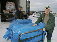 Saturday, Feb. 18, 2006  Anchorage, Alaska. Volunteer Iditarod Airforce pilot Reagan Russey and race manager Andy Willis  move straw to a waitng Cessna plane prior to flying them  out to checkpoints along the trail.  Each musher is given one bale of straw at a checkpoint to bed their dogs down.