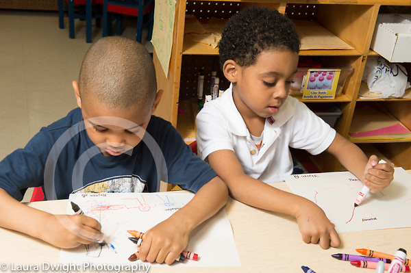 Education preschool 3-4 year olds, two boys drawing with markers side by side one using left hand and the other the right hand, both boys using fist grips