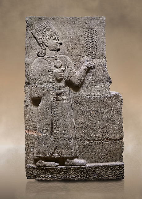 Photo of Hittite relief sculpted orthostat stone panel of Long Wall Basalt, Karkamıs, (Kargamıs), Carchemish (Karkemish), 900-700 B.C. Anatolian Civilisations Museum, Ankara, Turkey<br /> <br /> Goddess Kubaba. Goddess is depicted from the profile. She holds a pomegranate in her hands on her chest. She carries a one-horned headdress on her head. Her braided hair hangs down to her shoulder . <br /> <br /> On a brown art background.