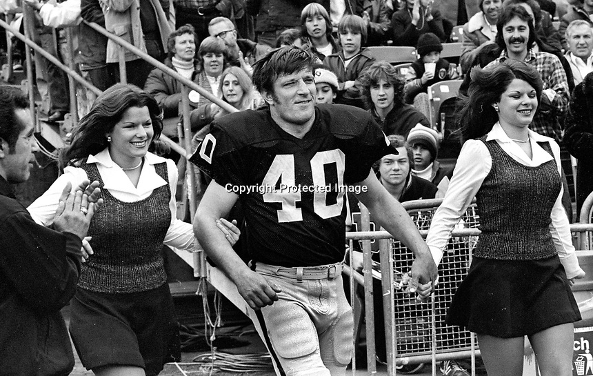 Raiders Pete Banaszak led onto the field by twins to get his award...(1975 pholto/Ron Riesterer)