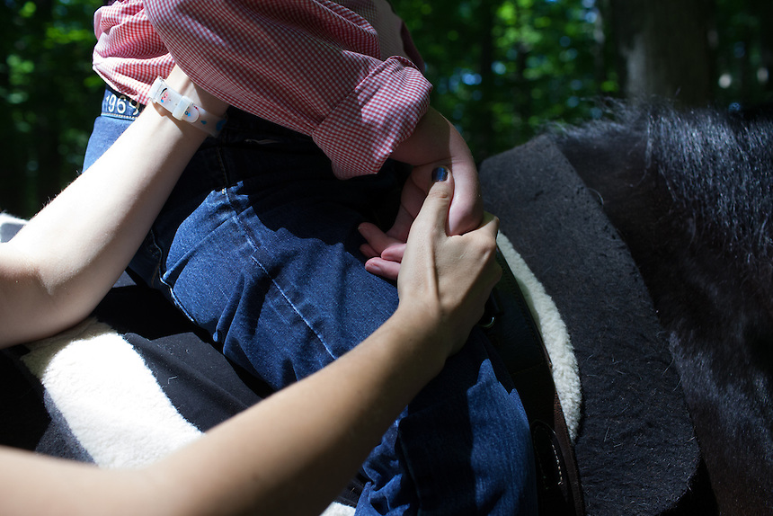 WASHINGTON, DC - JUNE 4, 2014: Detail of the hand of Christoph Ruesch, 31, held by assistant Alison Duvall while he rides a horse at Rock Creek Park as therapy for cerebral palsy. (Photo by Lance Rosenfield/Prime for The Washington Post)