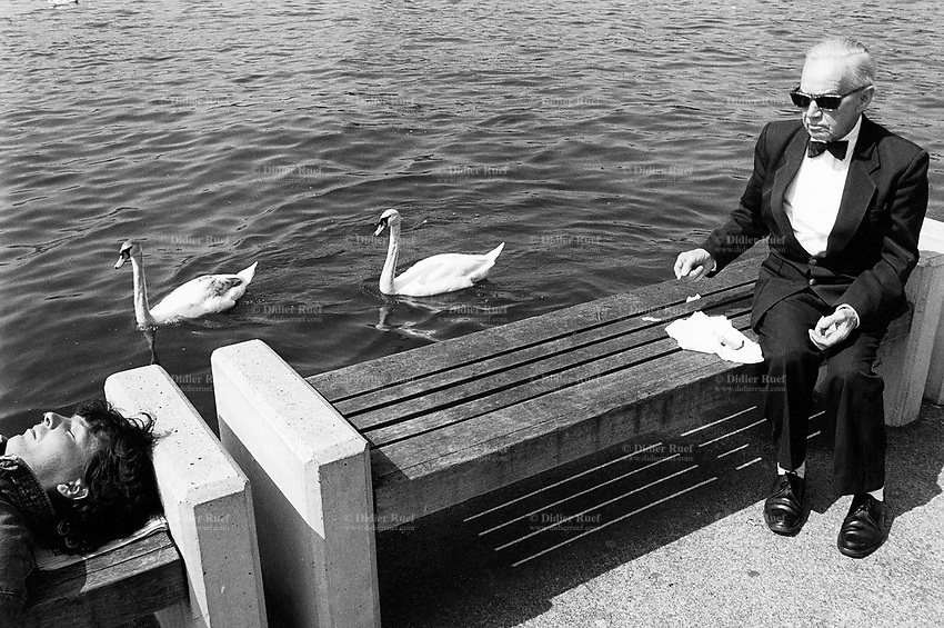 Switzerland. Zürich. An old man is dressed with a dinner jacket (evening suit) and a bow tie. He wears black sunglasses and is seated on a wood bench. He gives bread to two swans which are in the lake. Another man lays on his back and sleeps. © 1988 Didier Ruef