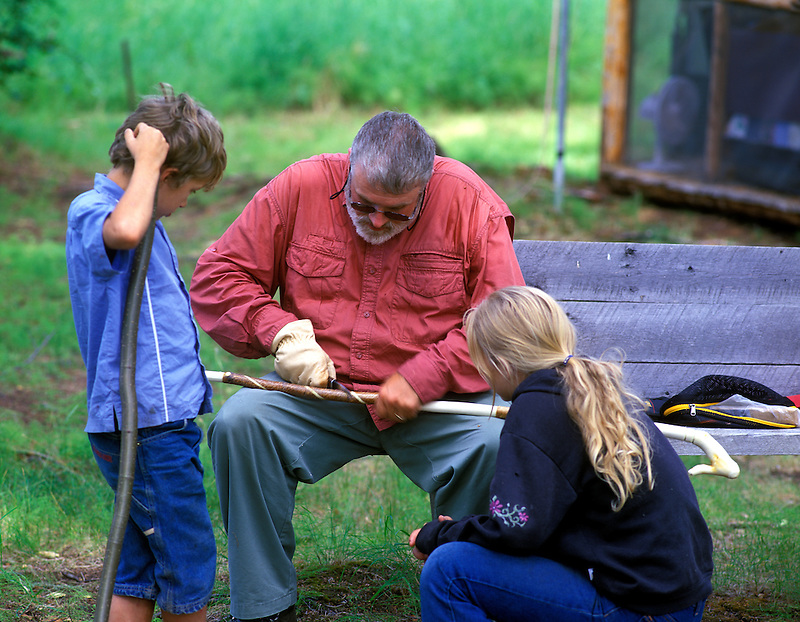 Man carving walking stick with children watching. Alaska