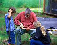 Man carving walking stick with children watching. Alaska