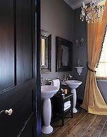 This boudoir-style bathroom is furnished with a pair of pedestal wash basins and graced with a crystal chandelier and full curtains with a tassel border