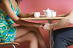 Couple holding hands, sitting at table in cafe