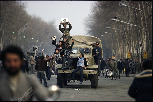 Jubilant men ride on an army truck after the announcement of the shah's departure. Tehran, January 16, 1979