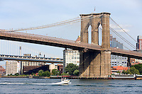 A small cruise ship travels under New York's Brooklyn Bridge.