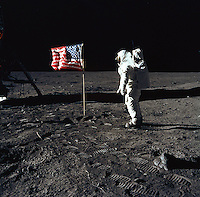 """(20 JULY 1969) --- Astronaut Edwin E. Aldrin, Jr., lunar module pilot of the first lunar landing mission, poses for a photograph beside the deployed United States flag during an Apollo 11 Extravehicular Activity (EVA) on the lunar surface. The Lunar Module (LM) is on the left, and the footprints of the astronauts are clearly visible in the soil of the Moon. Astronaut Neil A. Armstrong, commander, took this picture with a 70mm Hasselblad lunar surface camera. While astronauts Armstrong and Aldrin descended in the LM, the """"Eagle"""", to explore the Sea of Tranquility region of the Moon, astronaut Michael Collins, command module pilot, remained with the Command and Service Modules (CSM) """"Columbia"""" in lunar-orbit."""