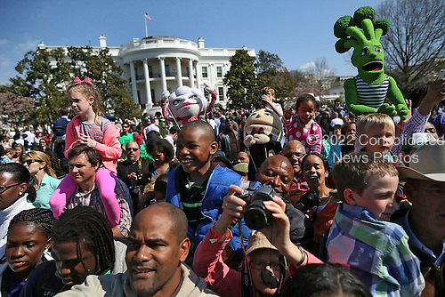 People watch as United States President Barack Obama reads a book to children during the annual Easter Egg Roll on the White House tennis court April 1, 2013 in Washington, DC. Thousands of people are expected to attend the 134-year-old tradition of rolling colored eggs down the White House lawn that was started by President Rutherford B. Hayes in 1878.  .Credit: Mark Wilson / Pool via CNP