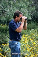 03848-00109 Man watching butterflies at flower gardens at Valley Nature Center Weslaco TX
