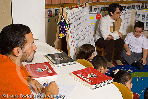 Preschool Headstart 4 year olds New York City male teacher taking notes in classroom horizontal