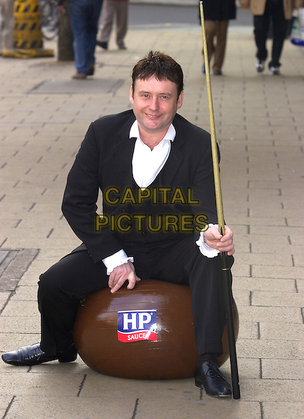 JIMMY BROWN (JIMMY WHITE) .Photocall to announce new snooker sponsership deal with HP Brown Sauce, as the official sponsors of the brown ball. Due to this new deal, Jimmy White has formally changed his name by deed poll to Jimmy Brown for one year!.New Zealand House, Haymarket, London, .February 8th 2005..full length cue sitting.Ref: PL.www.capitalpictures.com.sales@capitalpictures.com.©Capital Pictures.