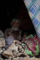 Old poor man hidding amongst old cloth in Bhaktapur, Layaku Nepal