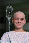 Portrait of young boy with cancer standing next to drip in hospital ward. MR