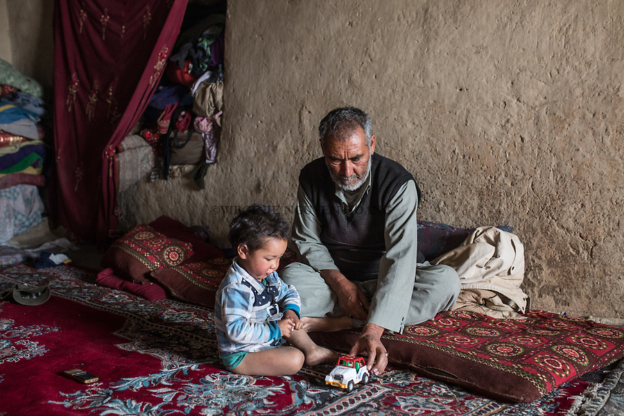 Mohammed Nabi plays with his youngest son Mhadi. Mohammed is Haina's husband and father of her 11 children. He has another wife who lives in Iran since several years, Yekalong, Afghanistan, 10th November 2017.<br /> <br /> Mohammed Nabi joue avec son cadet de 2 ans,Mahdi. Mohammed est le mari d'Hamina et p&egrave;re de ses 11 enfants. Il a une deuxi&egrave;me femme qui vit en Iran depuis plusieurs ann&eacute;es, Yekalong, Afghanistan, 10 Novembre 2017.