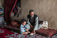 Mohammed Nabi plays with his youngest son Mhadi. Mohammed is Haina's husband and father of her 11 children. He has another wife who lives in Iran since several years, Yekalong, Afghanistan, 10th November 2017.<br /> <br /> Mohammed Nabi joue avec son cadet de 2 ans,Mahdi. Mohammed est le mari d'Hamina et père de ses 11 enfants. Il a une deuxième femme qui vit en Iran depuis plusieurs années, Yekalong, Afghanistan, 10 Novembre 2017.