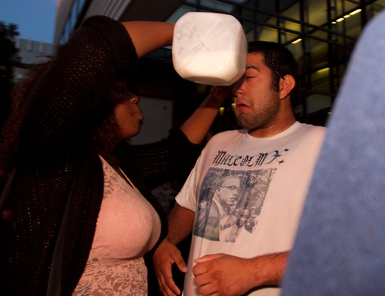Communications Major Priscillia Moon, 21, (CQ) treats Santa Monica College News Multimedia editor Paul Alvarez, Jr. with milk to counteract the effects of pepper spray after demonstrators rushed  campus police during an SMC Board of Trustees meeting April 3. 2012 at Santa Monica College in Santa Monica, Calif.  Alvarez had been recording the march, which started with around 54 protestors objecting to SMC's new two tier pay system that raises tuition on special core classes like Math and English, The march ended at the doors of the board room where police tried to maintain order and allow students who had arranged prior seating into the meeting. A lengthy discussion by members of the protest waffled between an orderly entry and anger that the Board had not chosen a larger venue to accommodate all. The flashpoint of confrontation occurred when ticketed students began entering and another group rushed the police at the door resulting in a pushing match between protestors and police that ended when pepper spray was used to clear the crowd. Two students were transported to hospital, five treated on scene for pepper spray irritation and many more were mildly affected including people in the boardroom. Alvarez was treated by Santa Monica city fire paramedics , but allowed other injured student go ahead of him in the treatment line, before returning to  filing the video for publication deadline. (Photo: Gerard Burkhart 818-207-0273)