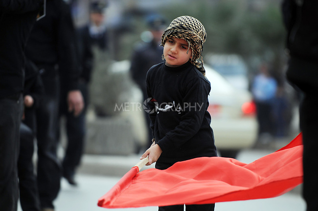 IRAQ, SULAIMANIYAH:  A boy waves a flag at the head of the marching worshippers...Around 500 hundred worshipers, many of them internally displaced Arabs, celebrated the Shia holiday of Ashura--the mourning of the death of the grandson of the Islamic prophet Mohammed.  ..Photo by Kamaran Najm/Metrography