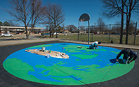 NWA Democrat-Gazette/BEN GOFF @NWABENGOFF<br /> Graham Edwards (right) and Steve Abb work on their mural Thursday, March 8, 2018, on the basketball court at Olive Street Park in Rogers. The Runway Group partnered with Rogers Parks and Recreation to paint the mural titled 'Space Jam: Earth to Mars,' wich shows the Earth under one basket, Mars under the oposite and the moon at center court. Design and painting of the mural is being done by Graham Edwards Art and Abb Custom Painting, with Abb's son Mike Abb also working on the piece.