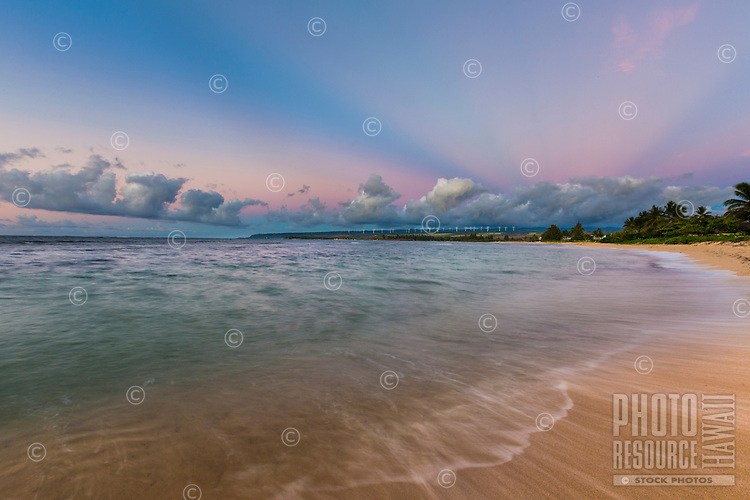 Colorful rays of light shine over a beach in Waialua at sunset, North Shore, O'ahu.