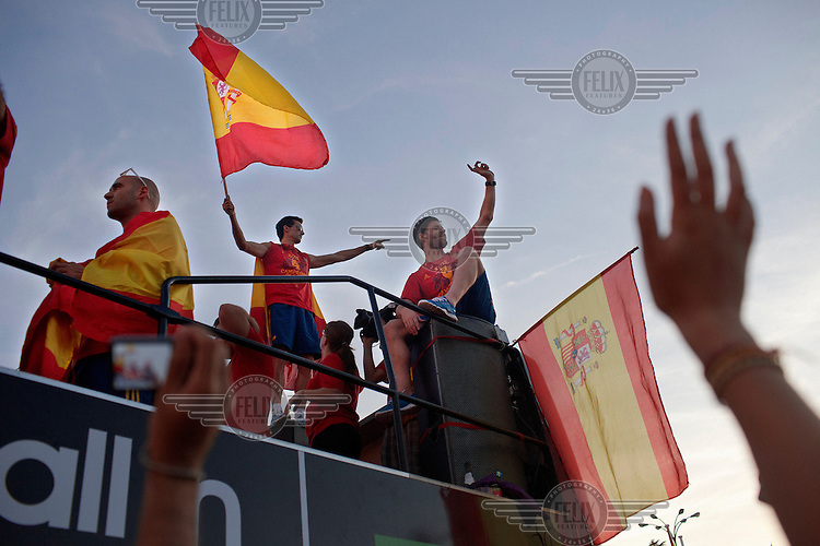 A player holds up the national flag during the victory parade of the Spanish national football team who won the UEFA EURO 2012 competition.