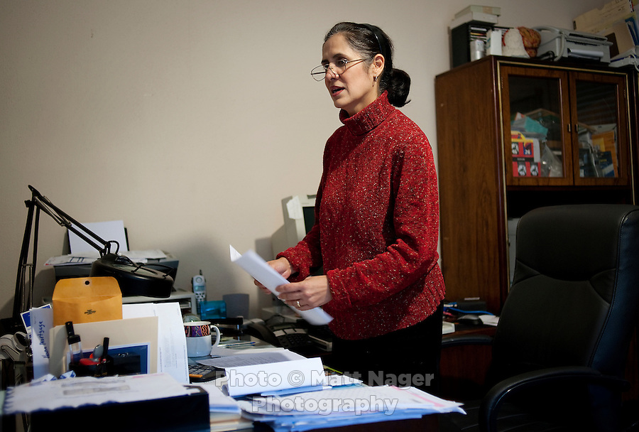 Martha Woodard (cq), at her home office in Laredo, Texas, US, Thursday, Dec. 10, 2009. Martha and her husband John Woodard were forced to move their office from the apartment complex they own and manage, to their home in order to rent out the original space to make more money. Because of the slumping economy, John is looking into getting another job to make ends meet. Martha, a native Spanish speaker from Mexico, is learning English, in part, to help take over managing their apartment business and be able to answer phone calls in English. ..PHOTOS/ MATT NAGER,