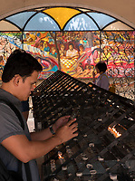 Inside the Baclaran Church in Manila, Philippines, a man and his Cellphone making images of his candles