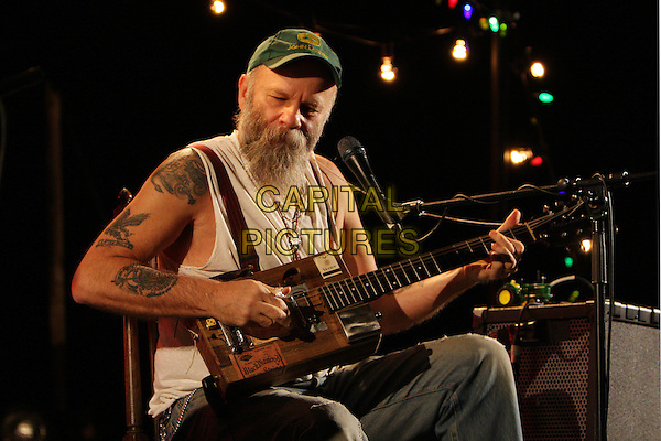 SEASICK STEVE.Live at the Hammersmith Apollo, London, England..January 31st, 2009.half length stage concert gig performance music beard facial hair green baseball cap hat white tank top guitar singing tattoos sitting.CAP/MAR.©Martin Harris/Capital Pictures.