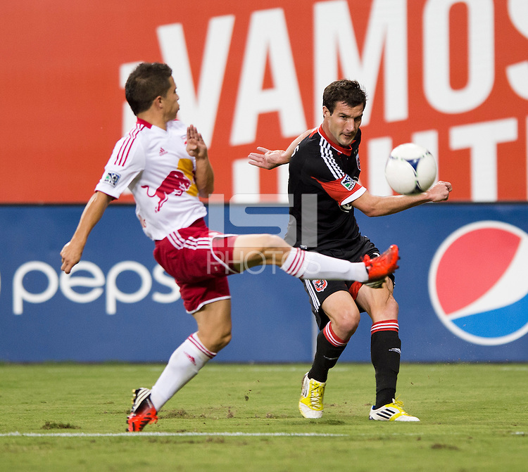 Chris Pontius (13) of D.C. United crosses the ball around Connor Lade (16) of the New York Red Bulls defending during the game at RFK Stadium in Washington, DC.  D.C. United tied the New York Red Bulls, 2-2.