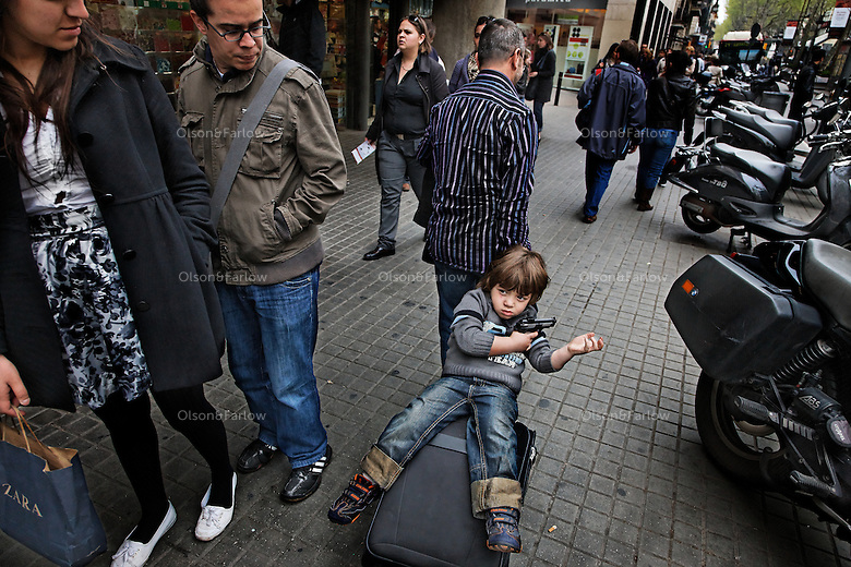 Street scenes in Barcelona in the neighborhood called Ramblas Catalunya.  A father takes his son on his roll-aboard to the bus.