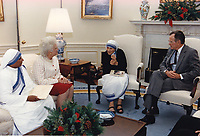 United States President George H.W. Bush, right, and first lady Barbara Bush, center left, meet with Mother Teresa, founder, Roman Catholic Missionaries of Charity, center right, in the Oval Office of the White House in Washington, D.C. on December 9, 1991.<br /> CAP/MPI/RS<br /> &copy;RS/MPI/Capital Pictures